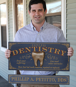 Dr. Petitto holding dentistry sign